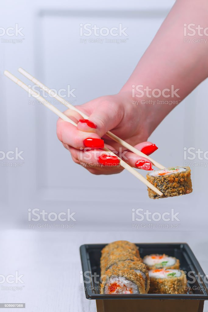 The female hand with magnificent manicure takes sushi from a black plate by means of wooden sticks стоковое фото