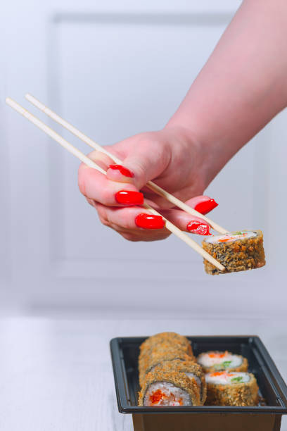 Cтоковое фото The female hand with magnificent manicure takes sushi from a black plate by means of wooden sticks