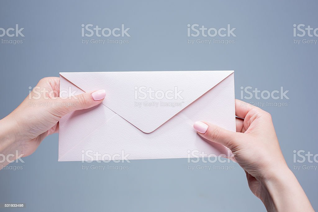 The female hands with envelope against the gray background stock photo