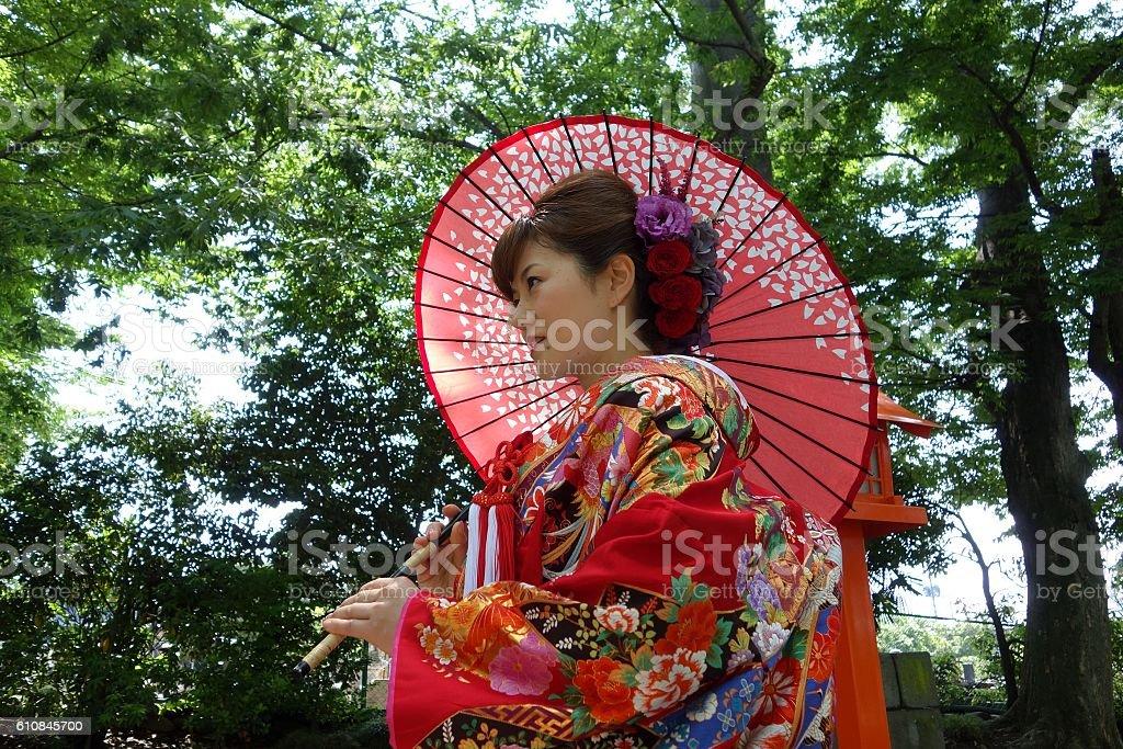 The female of colorful wedding kimono has a Japanese umbrella. - foto de stock