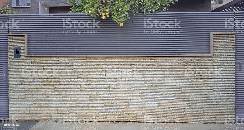 Taş bloklardan bir üçgen profili ile sac kombine çit stok fotoğrafı