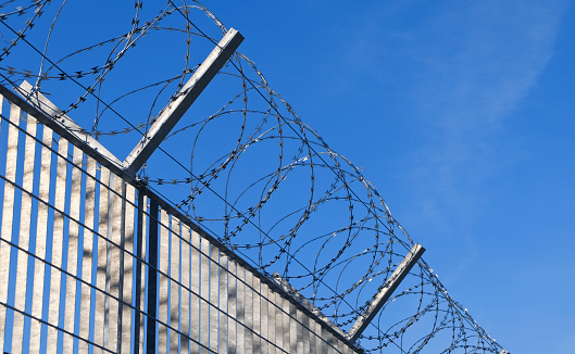 istock The Fence - Razor wire at the border 1155841779