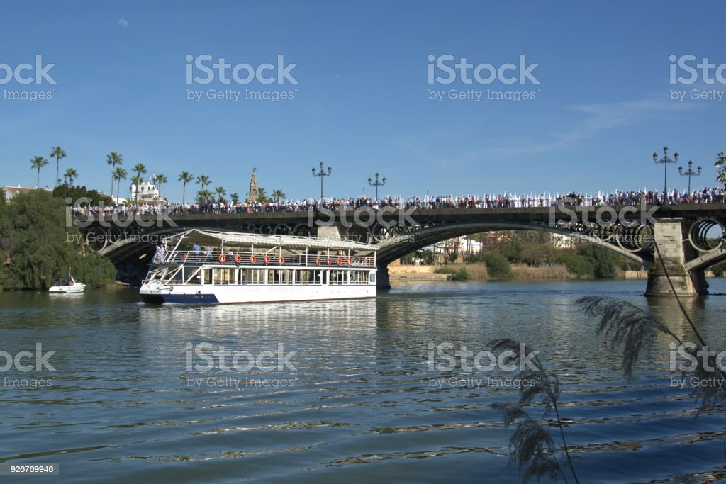 The ferry stops under the Triana bridge for the Easter procession stock photo