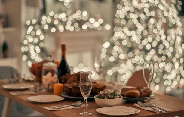 the festive table on the christmas tree background - pranzo di natale foto e immagini stock