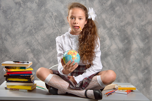 The fidget schoolgirl in school uniform sits on table and and holding a pencil in her teeth. Back to school. The new school year. Child education concept.