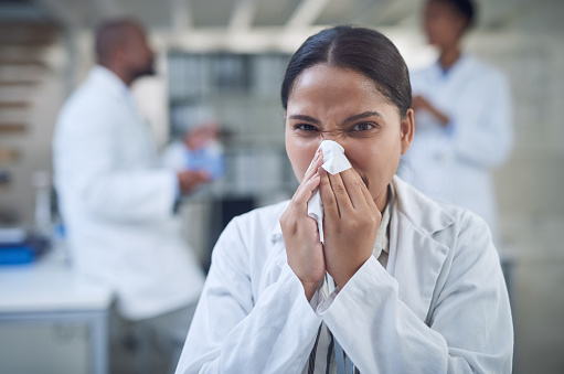 Shot of a young scientist blowing her nose with a tissue while working in a laboratory