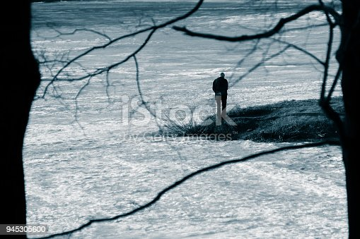 istock The figure of a lonely man in a black suit on a cape in the middle of a frozen pond. April, spring. Black and white toned photo 945305600