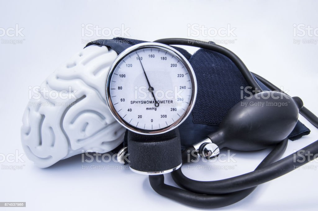 The figure of the human brain enveloped sphygmomanometer cuff with bulb (pear) and dial showing high pressure. Concept high brain or increased (raised) intracranial pressure (hypertension) stock photo