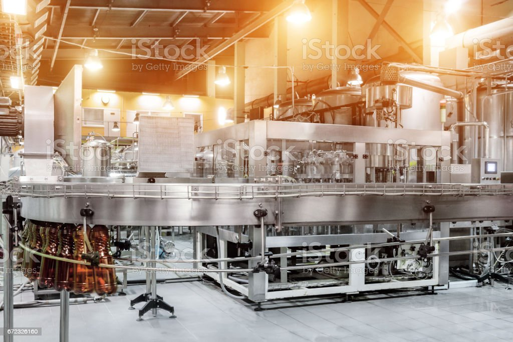 The filling machine pours beer into plastic PET bottles stock photo