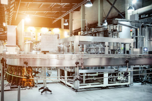 the filling machine pours beer into plastic pet bottles - factory stock photos and pictures