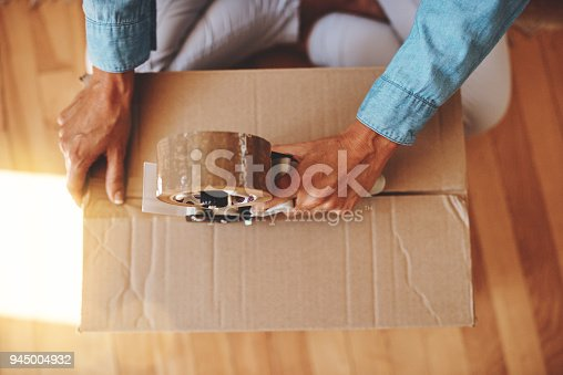 Cropped shot of a woman sealing a box with adhesive tape at home