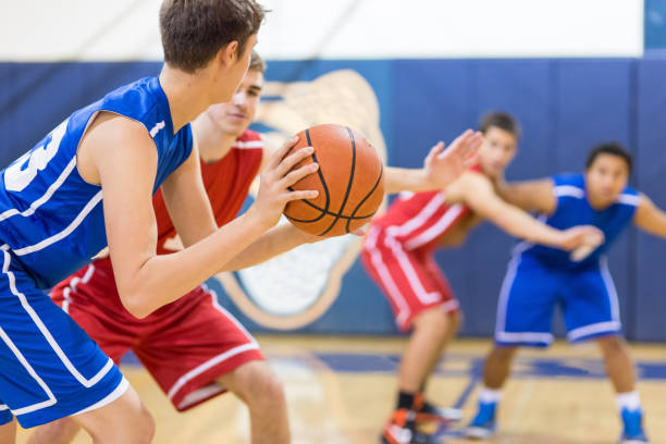 The final minutes... A high school basketball player holds the ball carefully outside the key as he's guarded. He's trying to decide who to pass to... basketball sport stock pictures, royalty-free photos & images