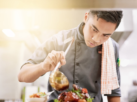 Cropped shot of a young male chef cooking in his kitchen