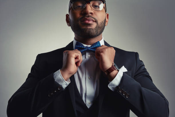 The final touches Cropped portrait of a handsome young businessman adjusting his bowtie while against a gray background bow tie stock pictures, royalty-free photos & images