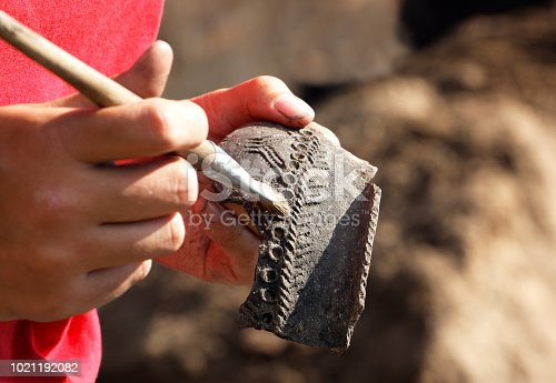 Archaeologist carefully handles the discovery - part of the medieval clay vessel.The pattern allows scientists to date the find