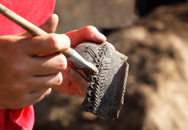 The find in the archaeological excavation is a piece of an ancient earthen vessel Archaeologist carefully handles the discovery - part of the medieval clay vessel.The pattern allows scientists to date the find archaeology stock pictures, royalty-free photos & images