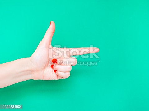 istock The Finger Gun Hand Sign. Is used as a way to say Yup with your hands. Pointing index finger on isolated turquoise green color background. 1144334804
