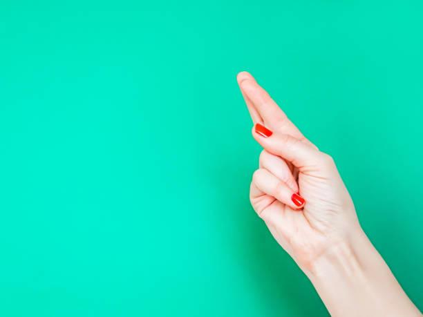 the fingers crossed hand sign. kreuzen sie die daumen, wenn sie auf glück hoffen. hand mit gekreuzten fingern. isoliert auf weißem hintergrund - wahre lügen stock-fotos und bilder