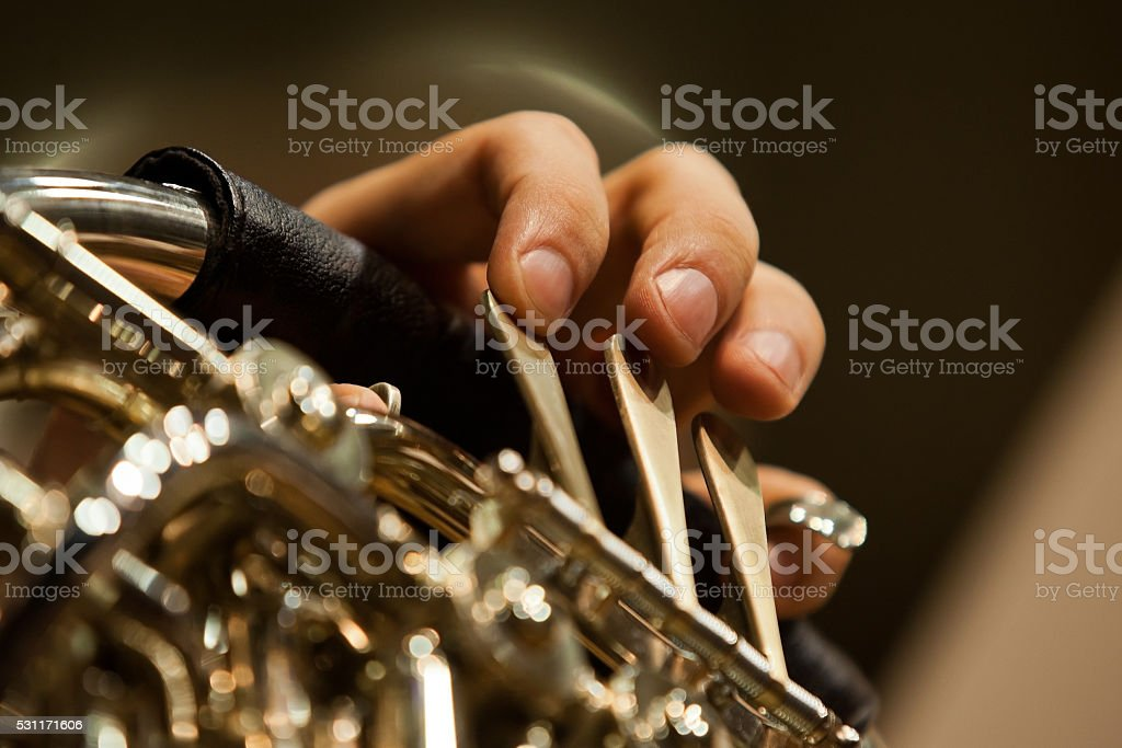 The fingers of the musician playing the French horn stock photo