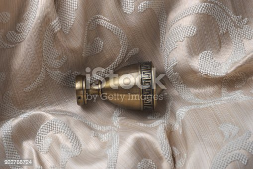 686515422istockphoto The finials for the curtain rods lies on the curtain fabric. 922766724