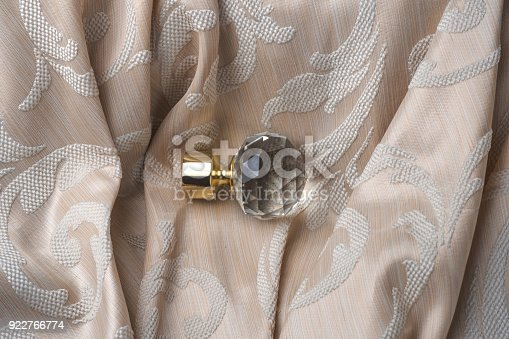 686515422istockphoto The finials for the curtain rods lies on the curtain fabric. 922766774