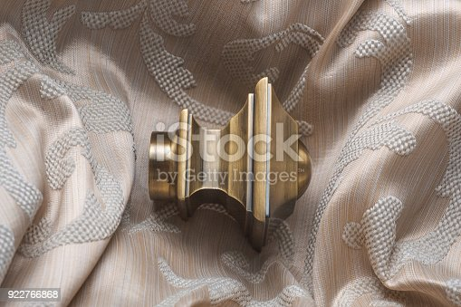 686515422istockphoto The finials for the curtain rods lies on the curtain fabric. 922766868