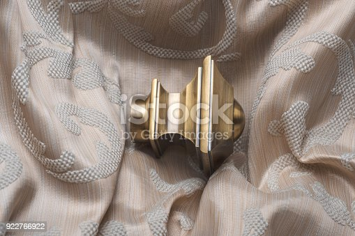 686515422istockphoto The finials for the curtain rods lies on the curtain fabric. 922766922