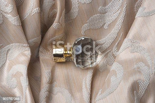 686515422istockphoto The finials for the curtain rods lies on the curtain fabric. 922767066
