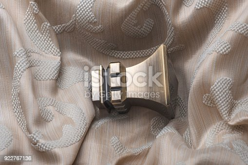 686515422istockphoto The finials for the curtain rods lies on the curtain fabric. 922767136