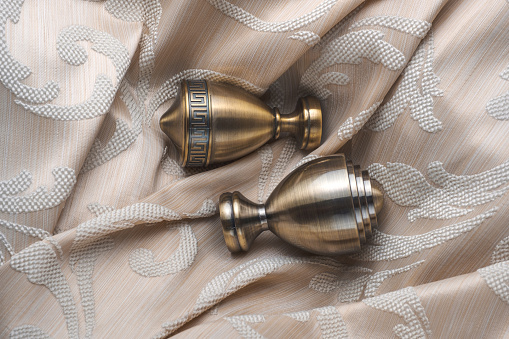 686515422 istock photo The finials for the curtain rods lies on the curtain fabric. 922767160