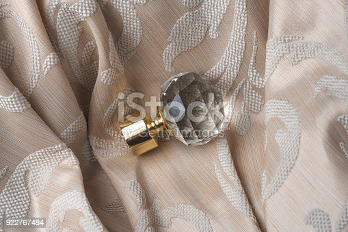 686515422istockphoto The finials for the curtain rods lies on the curtain fabric. 922767484