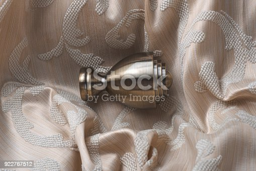 686515422istockphoto The finials for the curtain rods lies on the curtain fabric. 922767512