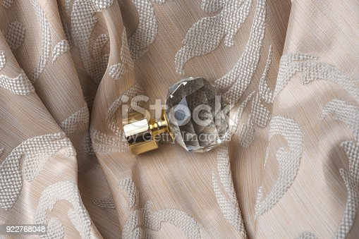 686515422istockphoto The finials for the curtain rods lies on the curtain fabric. 922768048