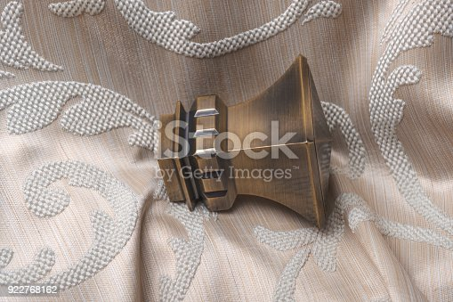 686515422istockphoto The finials for the curtain rods lies on the curtain fabric. 922768162