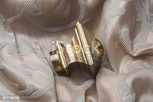 686515422istockphoto The finials for the curtain rods lies on the curtain fabric. 922768236