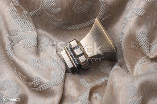 686515422istockphoto The finials for the curtain rods lies on the curtain fabric. 922768572
