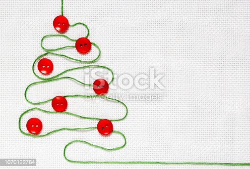 istock The fir tree of green threads on the white canvas is decorated with red buttons. 1070122764