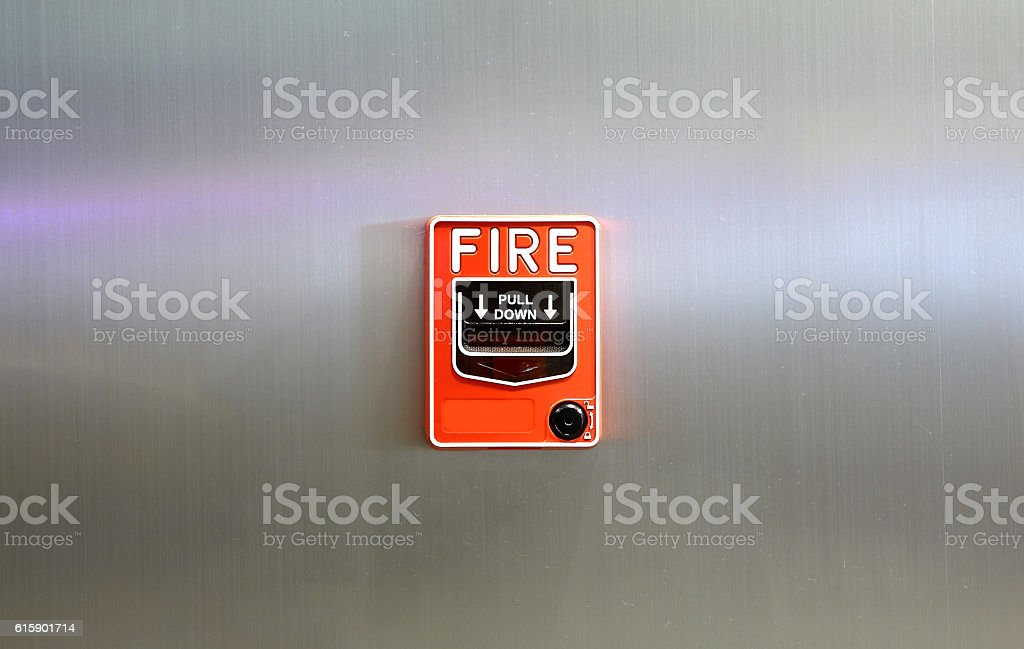 The Fire alarm embedded in the metal wall background