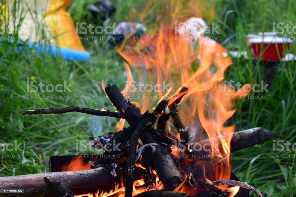 The fire in the time-worn brazier on green plants backgroun. Close-up. stock photo