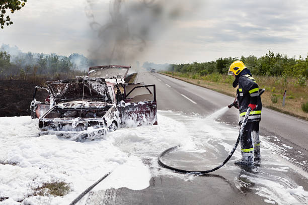 The Firefighter The firefighter battling with a fire on the car extinguishing stock pictures, royalty-free photos & images