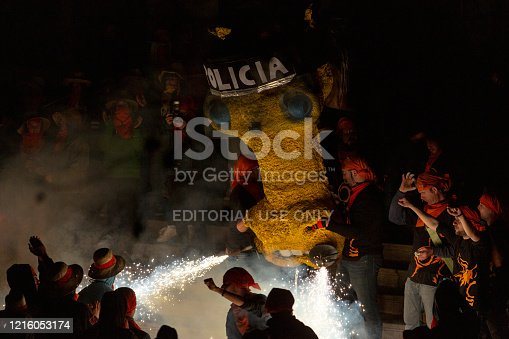 The firework beast of Molins de Rei throwing sparks from his nose one party night. Shot in Barcelona Province, Spain. The beast is costumized with a police helmet. Some people stands, run and dance around it