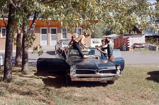 Near Ames, Iowa, USA, 1979. A young car owner washes his first car with his friends.