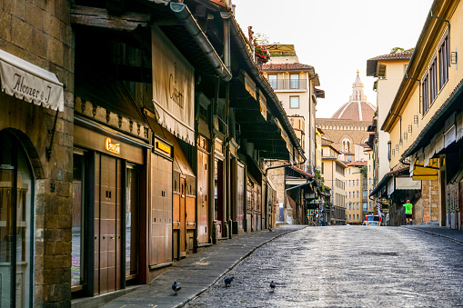 The first lights of the day illuminate the artisan goldsmith shops along Ponte Vecchio in Florence
