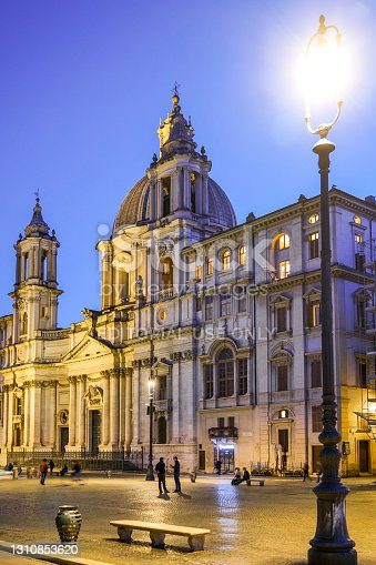 Rome, Italy, March 30 -- The first lights of the evening illuminate Piazza Navona, the Fountain of the Four Rivers and the church of Sant'Agnese, masterpieces of the Roman Baroque. This place in the heart of Rome is much loved by residents and tourists for the presence of many typical restaurants and for the monumental beauty of one of the most famous squares in the world. Image in high definition format.