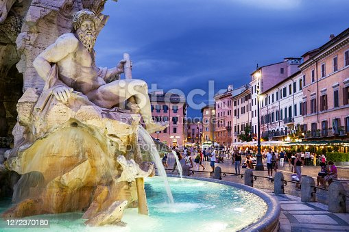 Rome, Italy, September 11 -- The first lights of the evening illuminate Piazza Navona while rain clouds gather in the sky, with the Gianlorenzo Bernini's fountain of the Four Rivers. This iconic square in the heart of Rome is much loved by residents and tourists for the presence of many typical restaurants of Roman cuisine and for the monumental beauty of one of the most beautiful squares in the world. Image in High Definition format.