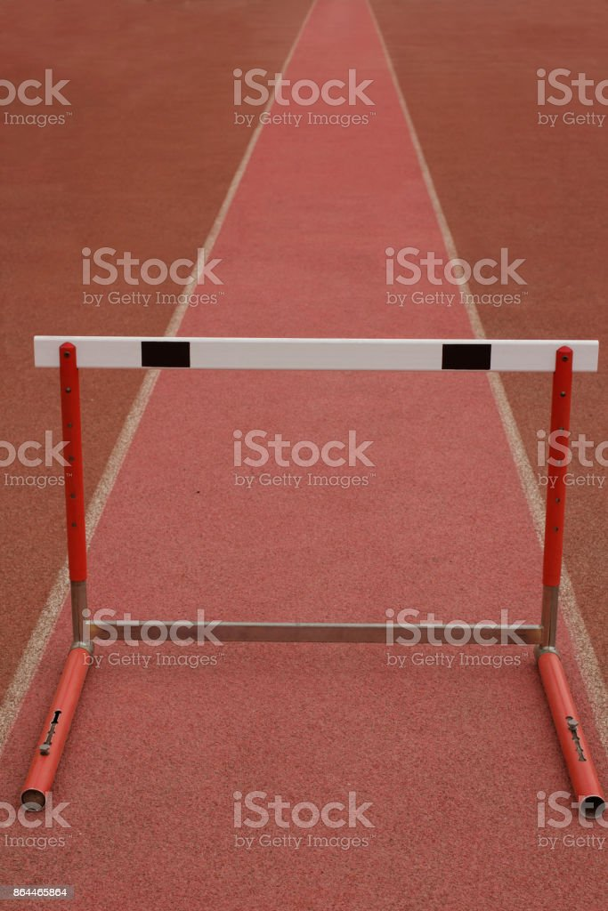The first obstacle. Concept with one hurdle on red track. stock photo