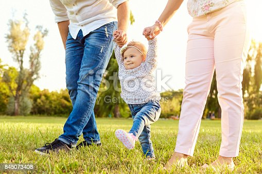 istock The first steps of the baby.  A happy family. 845073408