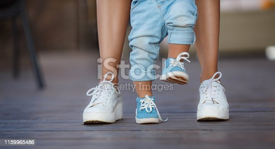 Mom in white sneakers with a young son, dressed in blue pants and blue shoes, a warm summer day and learn to walk in the street, the first steps, the mother maintains her son.
