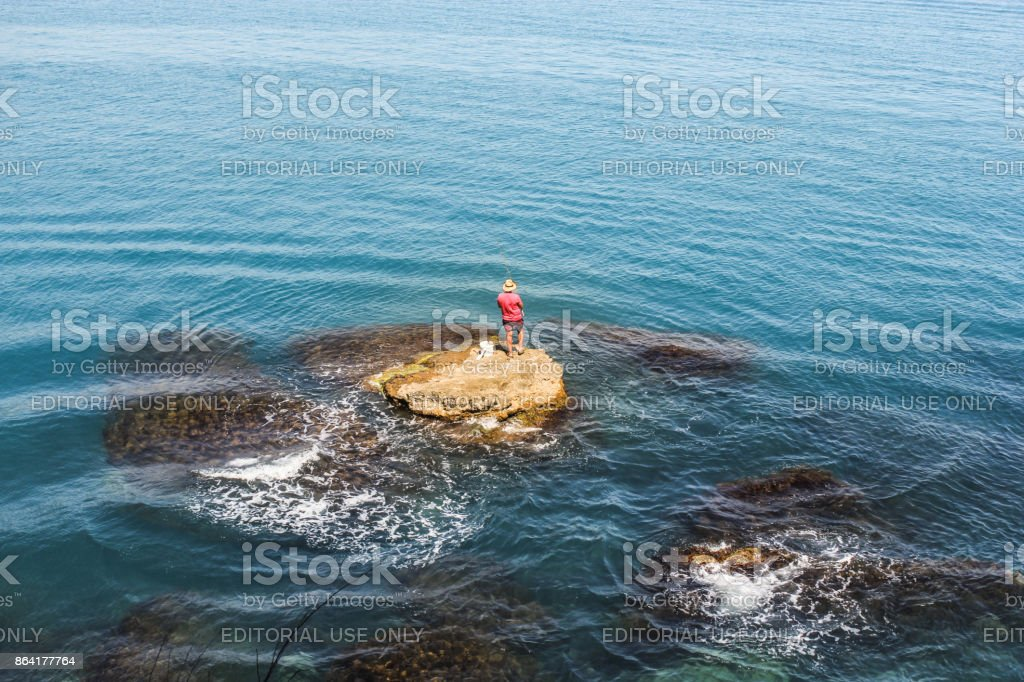 The fisherman on a stone. royalty-free stock photo