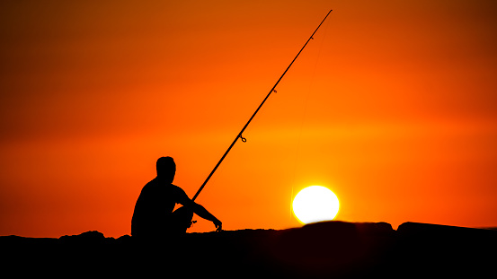 A fisherman watches the sunset as he's fishing